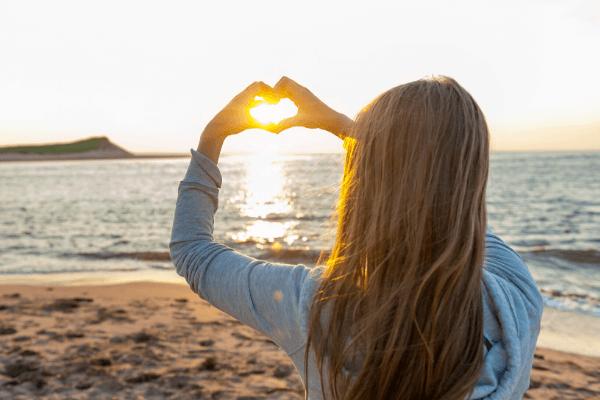 Hopeful girl holding hands in heart shape